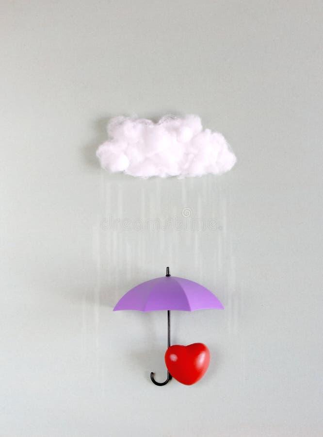 Röd hjärta under det purpurfärgade paraplyet arkivbild