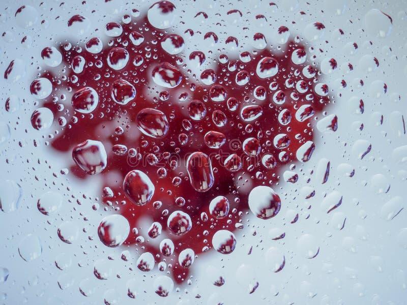 Röd hjärta under vattensmå droppar arkivfoton