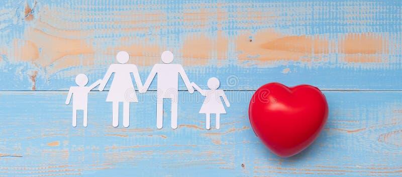 Röd hjärtaform med familjpapper på blå träbakgrund för pastellfärgad färg royaltyfri bild