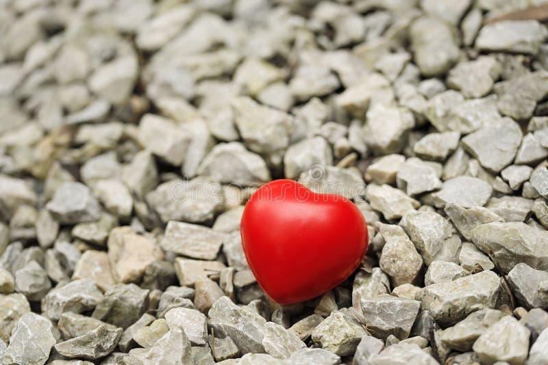 Röd hjärtaform på grusbakgrund royaltyfria bilder