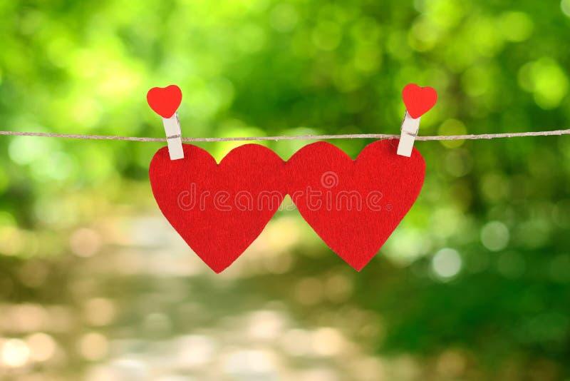 Röd hjärtaform som hänger, över den naturliga bakgrunden fotografering för bildbyråer