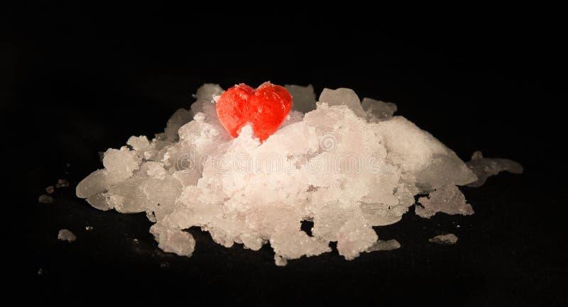 Röd ishjärta på en snöhög arkivfoto