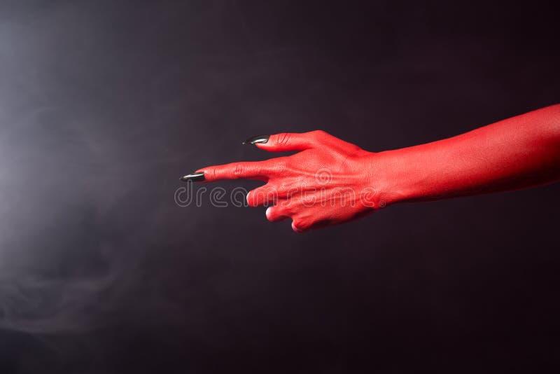 Röd jäkel som pekar handen med svart kors, spikar, före detta royaltyfri fotografi