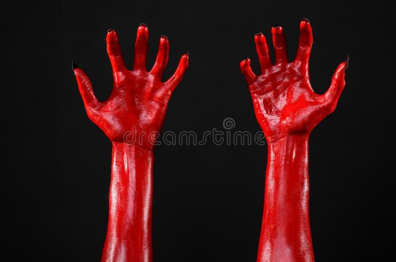Röd jäkels händer med svart spikar, röda händer av Satan, allhelgonaaftontema, på en svart bakgrund som isoleras royaltyfria bilder
