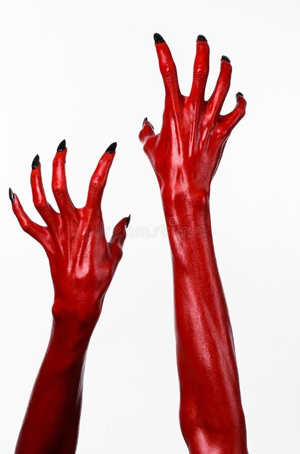 Röd jäkels händer med svart spikar, röda händer av Satan, allhelgonaaftontema, på en vit bakgrund som isoleras royaltyfria foton
