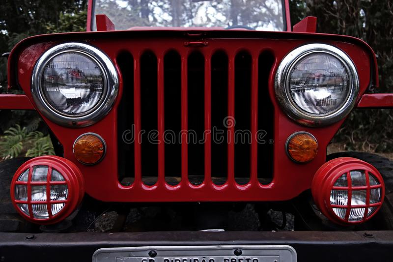 Röd jeep - den antika jeepskyddsgallret och billyktor - antikt jeepframdelfoto royaltyfri foto