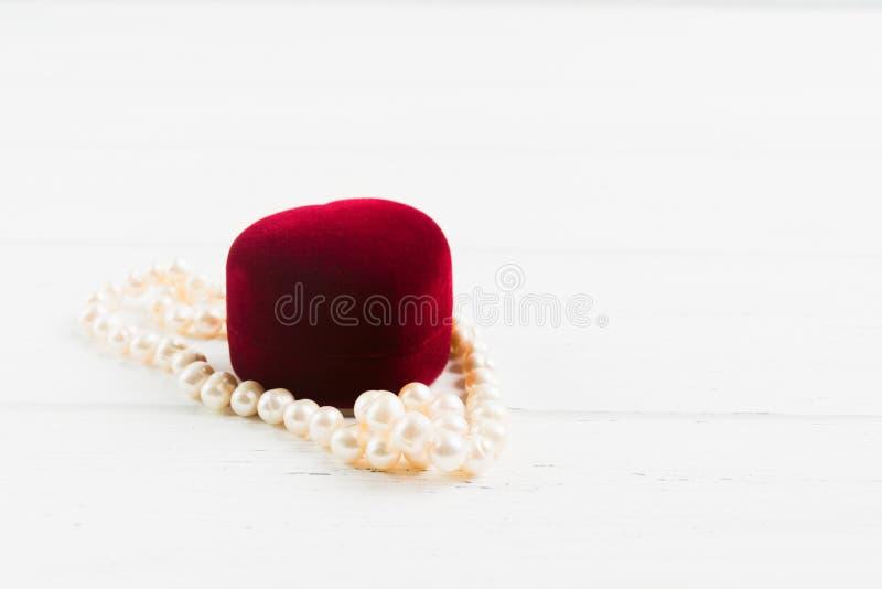 Röd jewellry ask med pärlahalsbandet på träbakgrund arkivbilder