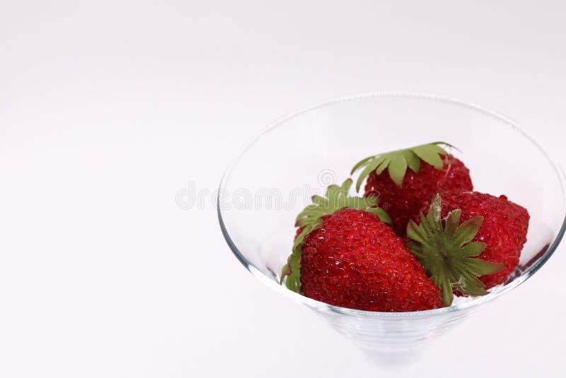 Röd jordgubbe i ett exponeringsglasexponeringsglasexponeringsglas på en vit bakgrundsnärbild efterföljdjordgubbar placera text royaltyfri fotografi