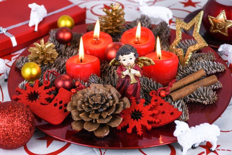 Röd jul dekorerade kransplattan med fyra brinnande stearinljus på en tabelltorkduk som omgavs med vita får arkivbild