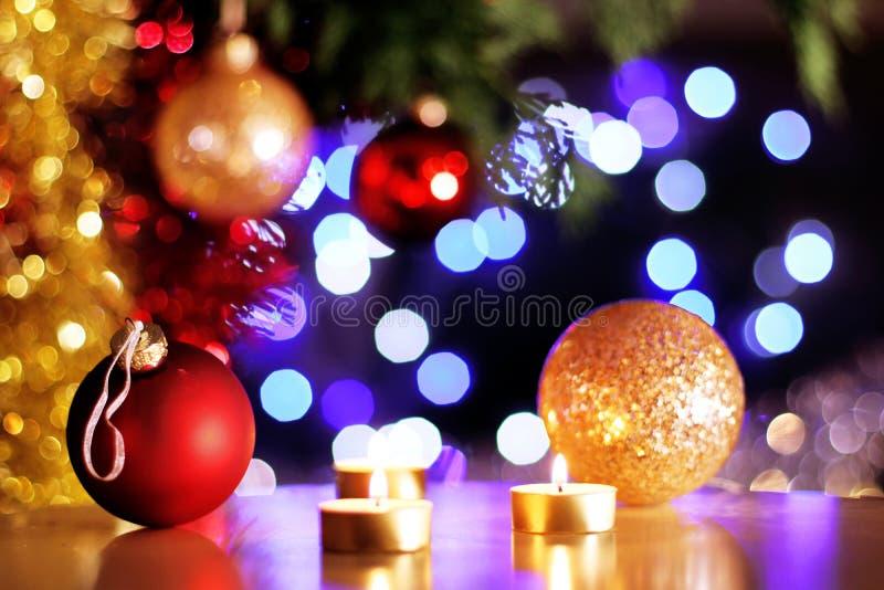 Röd jul och guld- struntsaker med guld- stearinljus och träd som gristrar ljus i bakgrund royaltyfri foto