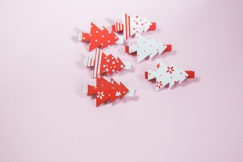 Röd jul och vitklämmor på rosa bakgrund ekologiskt trä för julgarneringar close upp fotografering för bildbyråer