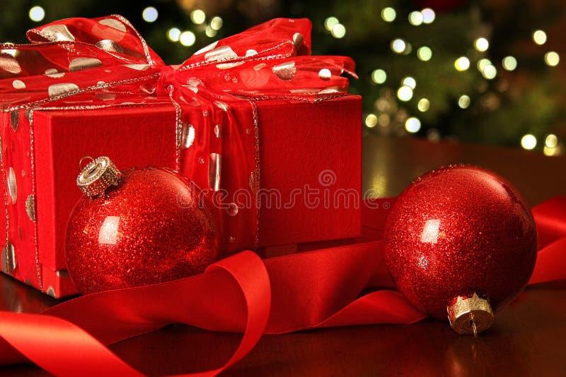 Röd julgåva med prydnadar royaltyfria bilder