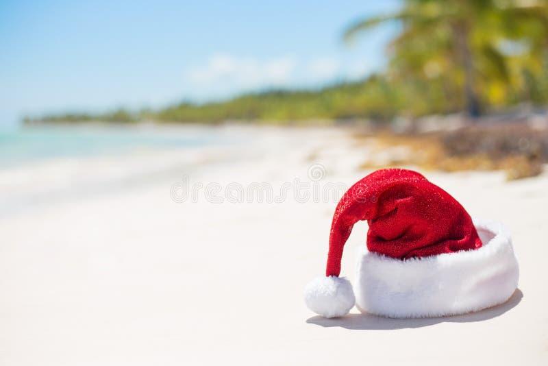 Röd julhatt på stranden arkivbild
