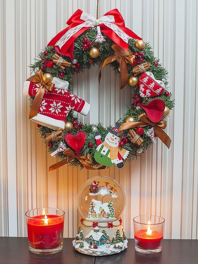 Röd julkrans med garneringar, stearinljus, musikalisk boll för snö fotografering för bildbyråer