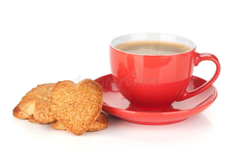 Röd kaffekopp och hjärta formade kakor royaltyfria bilder