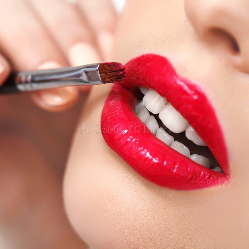 Röd kantcloseup för kvinna. Makeup fotografering för bildbyråer