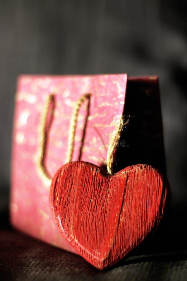 Röd karvad trähjärta och en rosa gåvaask fotografering för bildbyråer