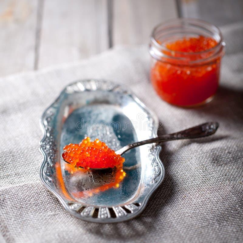 Röd kaviar för lax i en glass krus och sked arkivbild