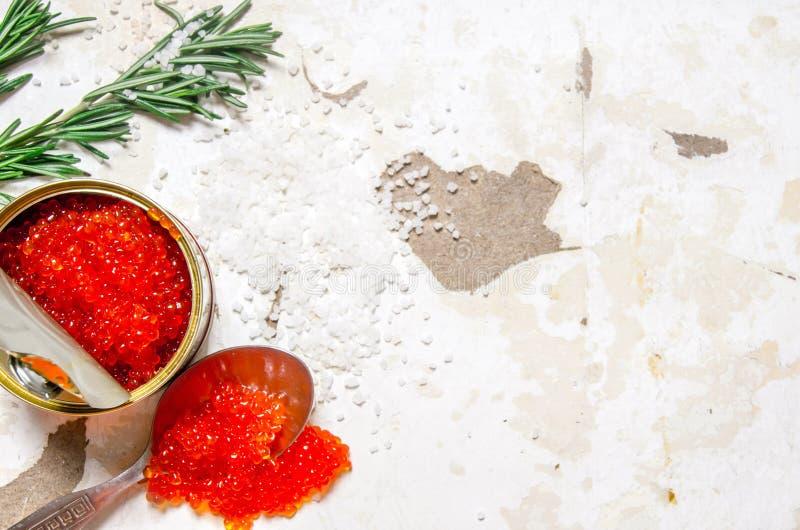 Röd kaviar i en krus med en sked royaltyfria bilder
