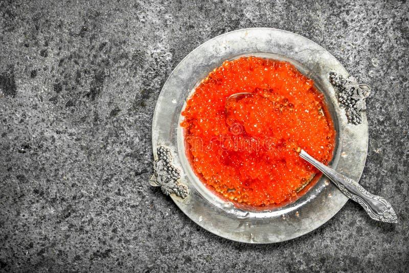 Röd kaviar i ett gammalt tefat fotografering för bildbyråer