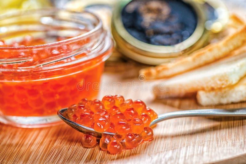 Röd kaviar och kaviar Sked av röd kaviar och öppna cans av cavi royaltyfria bilder