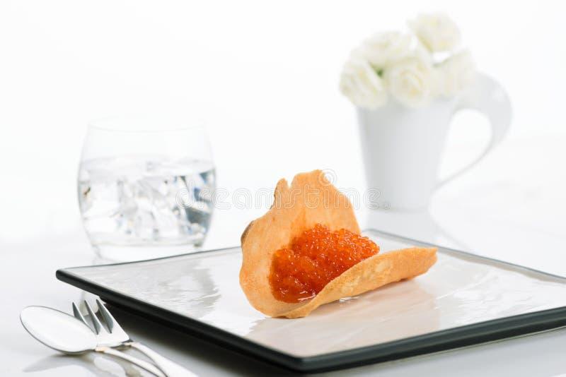Röd kaviar på en fyrkantig keramisk stilfull platta arkivfoto