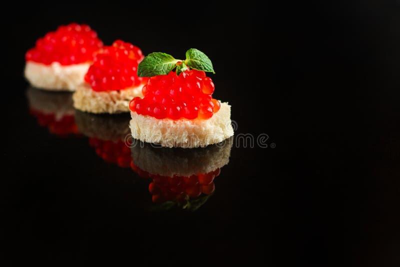 Röd kaviarcanape eller smörgås med den röda mellanmållaxfisken, skaldjur många bakgrundsklimpmat meat mycket Top beskådar arkivfoto