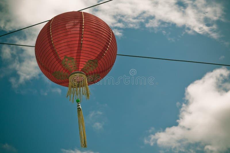 Röd kinesisk pappers- lykta mot en blå himmel royaltyfri bild