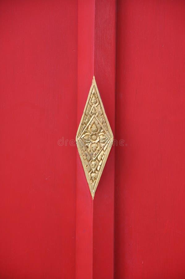 Röd kinesisk tempeldörr med den utsmyckade mässingsplattan royaltyfria foton