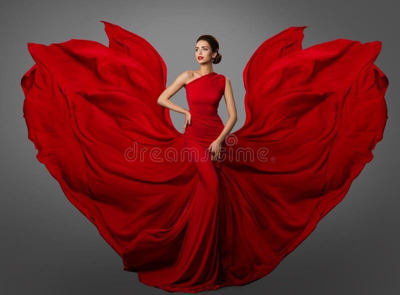 Röd klänning för kvinna, modemodell i långa siden- vinkande kappavingar som flyger fladdra tyg arkivfoton