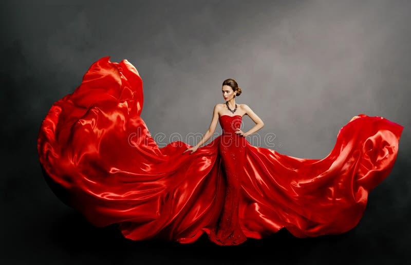 Röd klänning för kvinna, modemodell i vinkande torkduk för lång siden- kappa på vind som flyger tyg royaltyfri bild