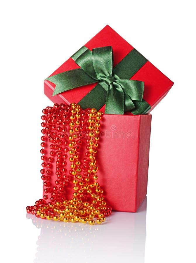 Röd klassisk gåvaask med den gröna satängpilbågen och pärlor royaltyfri foto