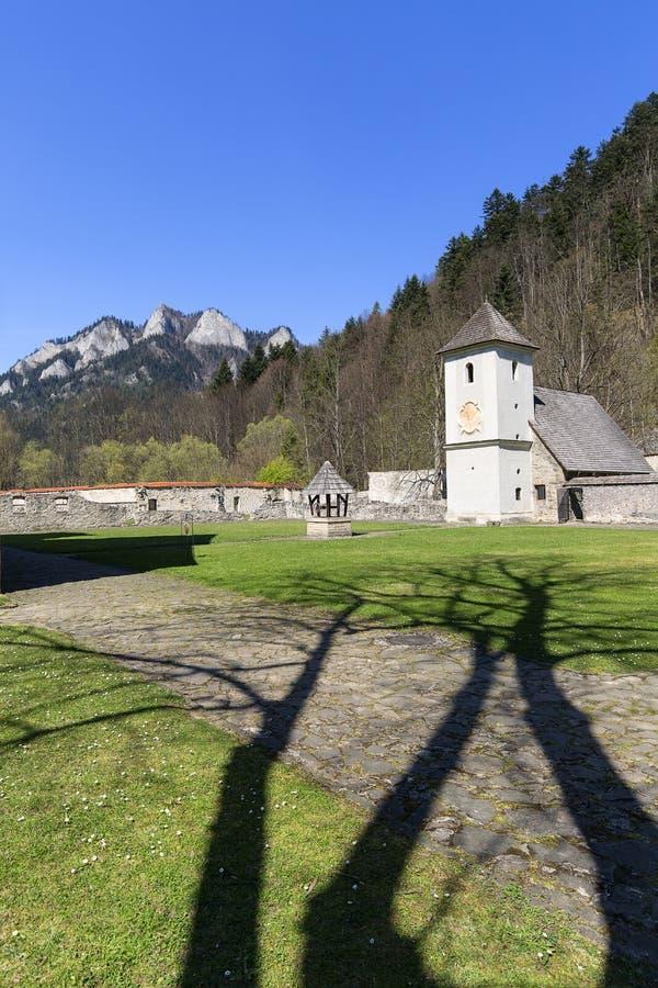 Röd kloster, klockatorn, omgeende vägg och sikt på tre kronor massiv, Slovakien royaltyfri bild