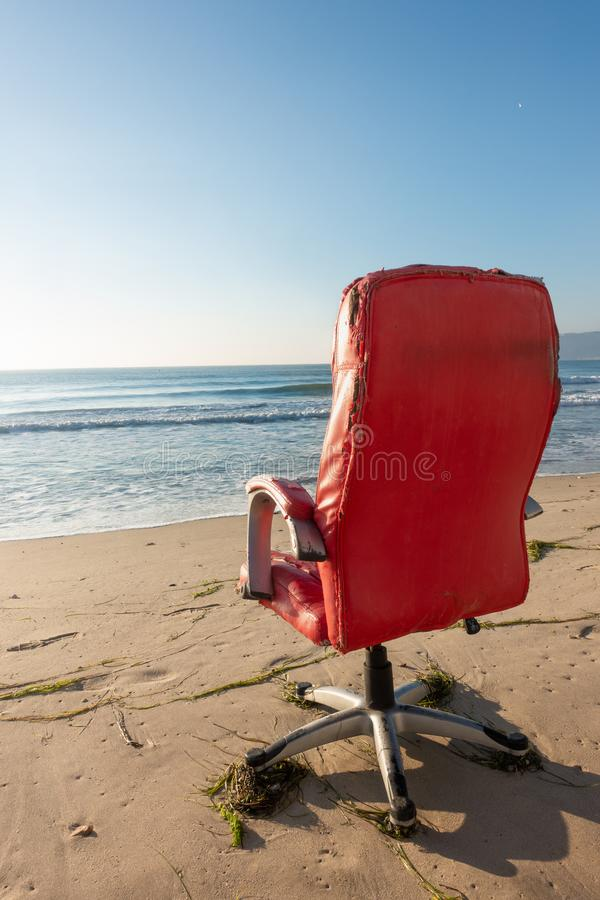 Röd kontorsstol på stranden fotografering för bildbyråer