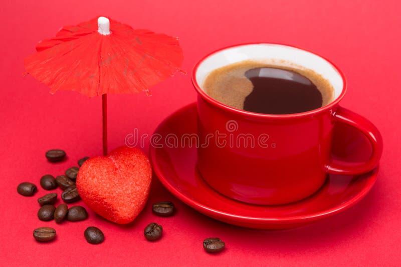 Röd kopp med en drink av kaffe med skum på en röd bakgrund, nära kaffebönor under ett dekorativt paraply och röda marshmallower m arkivbilder