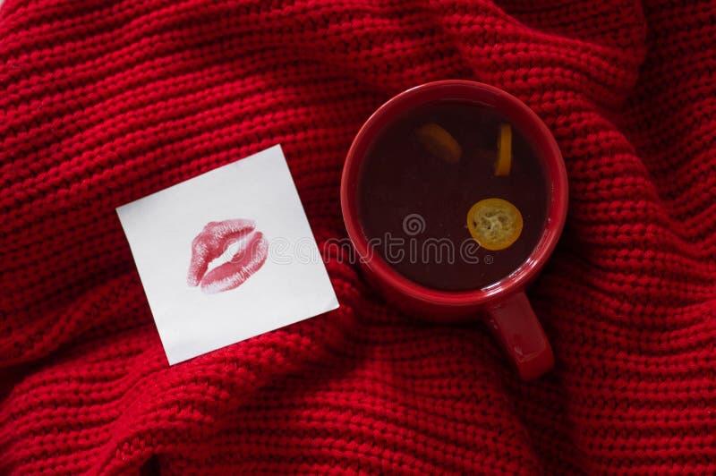 Röd kopp te och en anmärkning med en kyss på en röd bakgrund hjärta för gåvan för dagen för begreppet för den blåa asken för bakg arkivfoto
