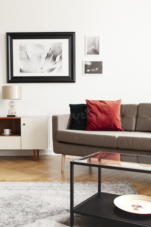 Röd kudde på soffan bredvid det vita kabinettet med lampan i vardagsruminre med affischer Verkligt foto royaltyfri fotografi