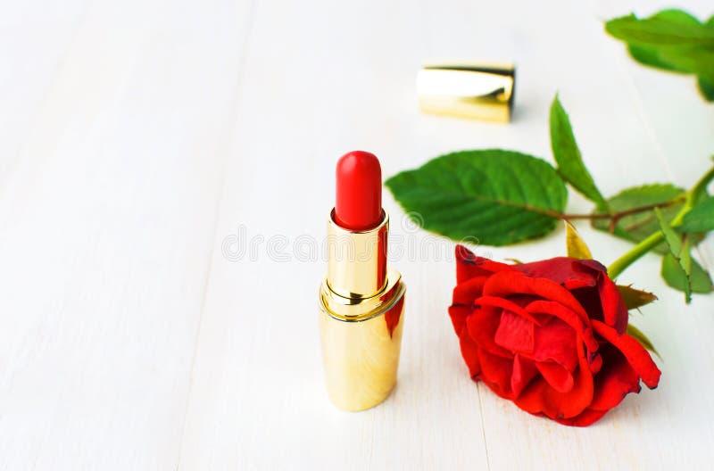 Röd läppstift med röda rosor på rosa bakgrund med kopieringsutrymme Lekmanna- lägenhet för bästa sikt för makeuptillbehör Olika k royaltyfria bilder