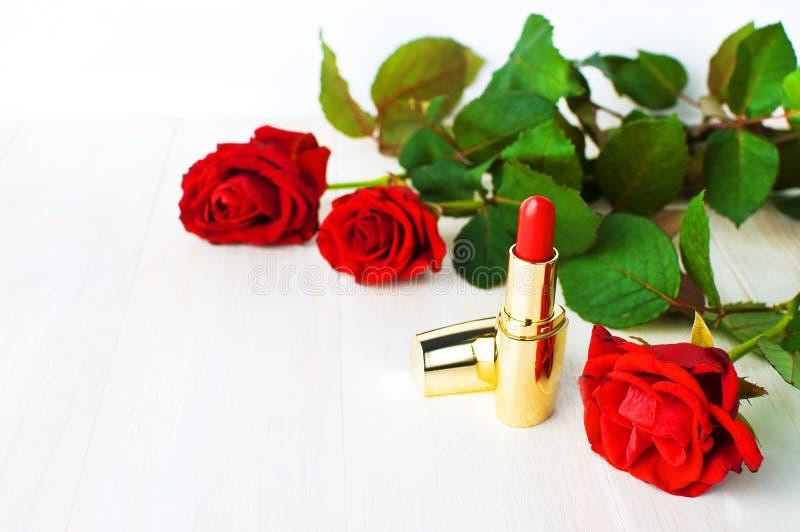 Röd läppstift med röda rosor på rosa bakgrund med kopieringsutrymme Lekmanna- lägenhet för bästa sikt för makeuptillbehör Olika k royaltyfri foto
