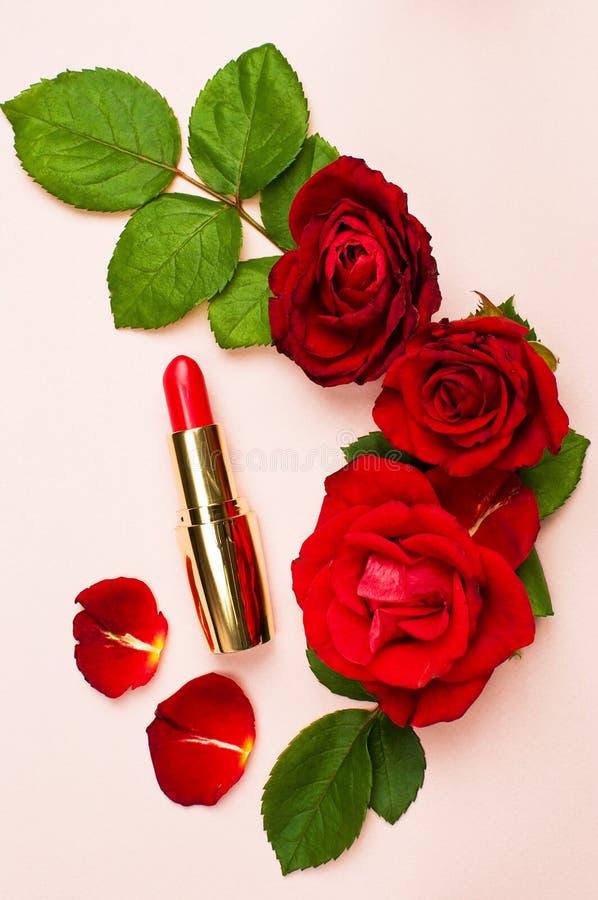 Röd läppstift med röda rosor på rosa bakgrund med kopieringsutrymme Lekmanna- lägenhet för bästa sikt för makeuptillbehör Olika k royaltyfri bild