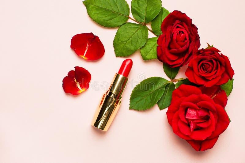 Röd läppstift med röda rosor på rosa bakgrund med kopieringsutrymme Lekmanna- lägenhet för bästa sikt för makeuptillbehör Olika k arkivbilder