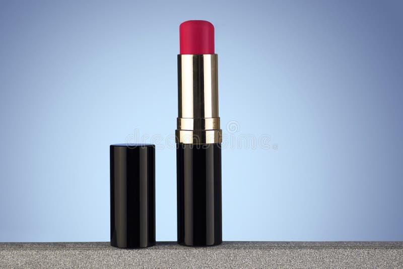 Röd läppstift som isoleras på ljus - blå lutningbakgrund fotografering för bildbyråer