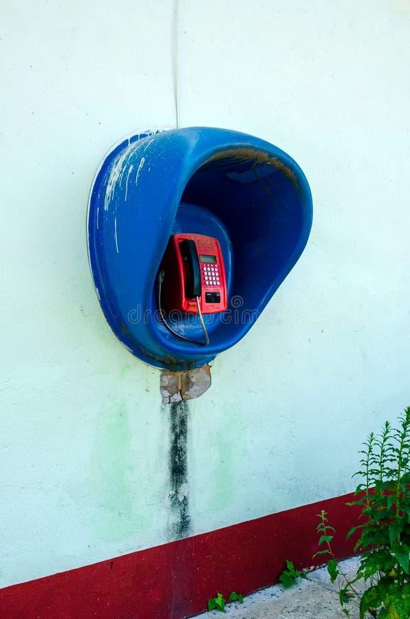 Röd löntelefon på en stadsgata arkivbilder
