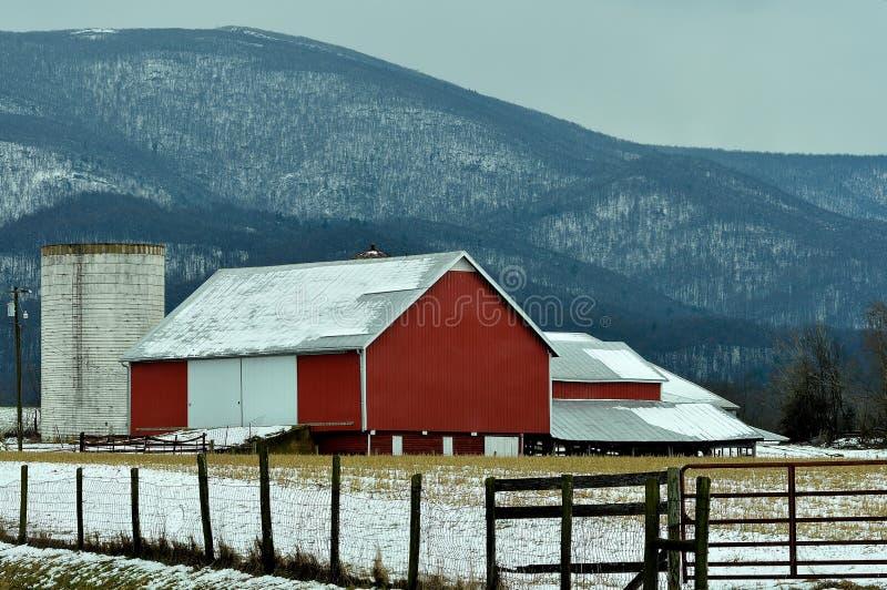 Röd ladugård efter en sen vintersnö royaltyfri fotografi