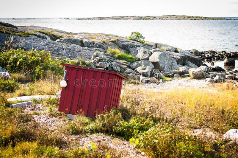 Röd ladugård för ensam falun på kusten av Sverige fotografering för bildbyråer