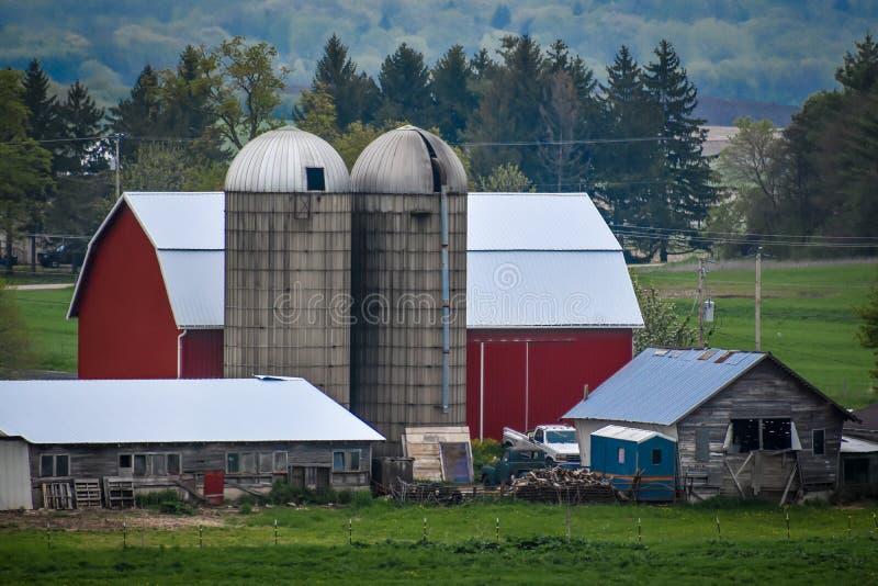 Röd ladugård med två silor arkivfoto