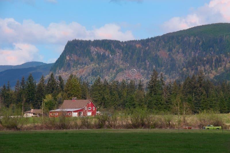 Röd ladugård och bergskedja arkivfoton