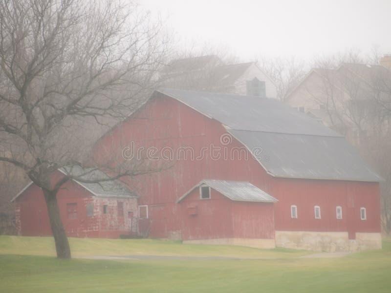 Röd ladugård på dimmig dimmig morgon arkivfoton
