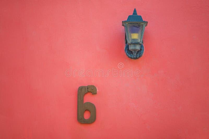 R?d lampa och siffra sex 6 p? den r?da v?ggen arkivfoto