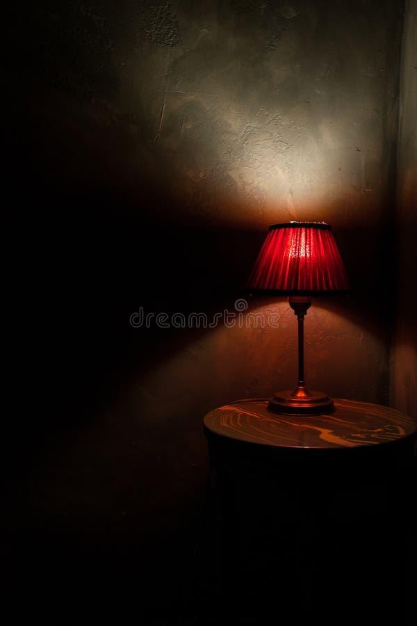 Röd lampa på en brunt, rund tabell royaltyfri foto